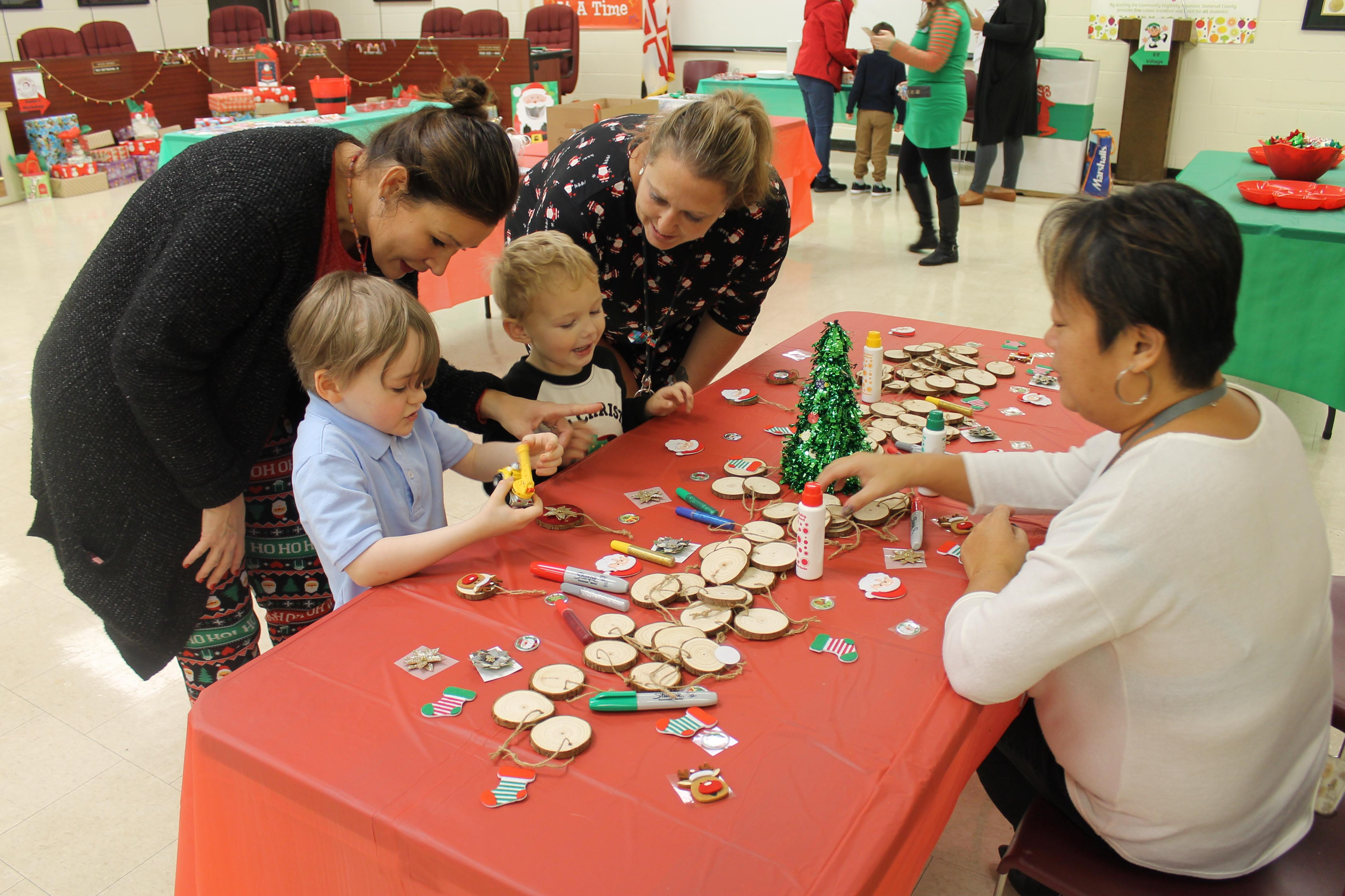 children and adults at a table making Christmas ornaments