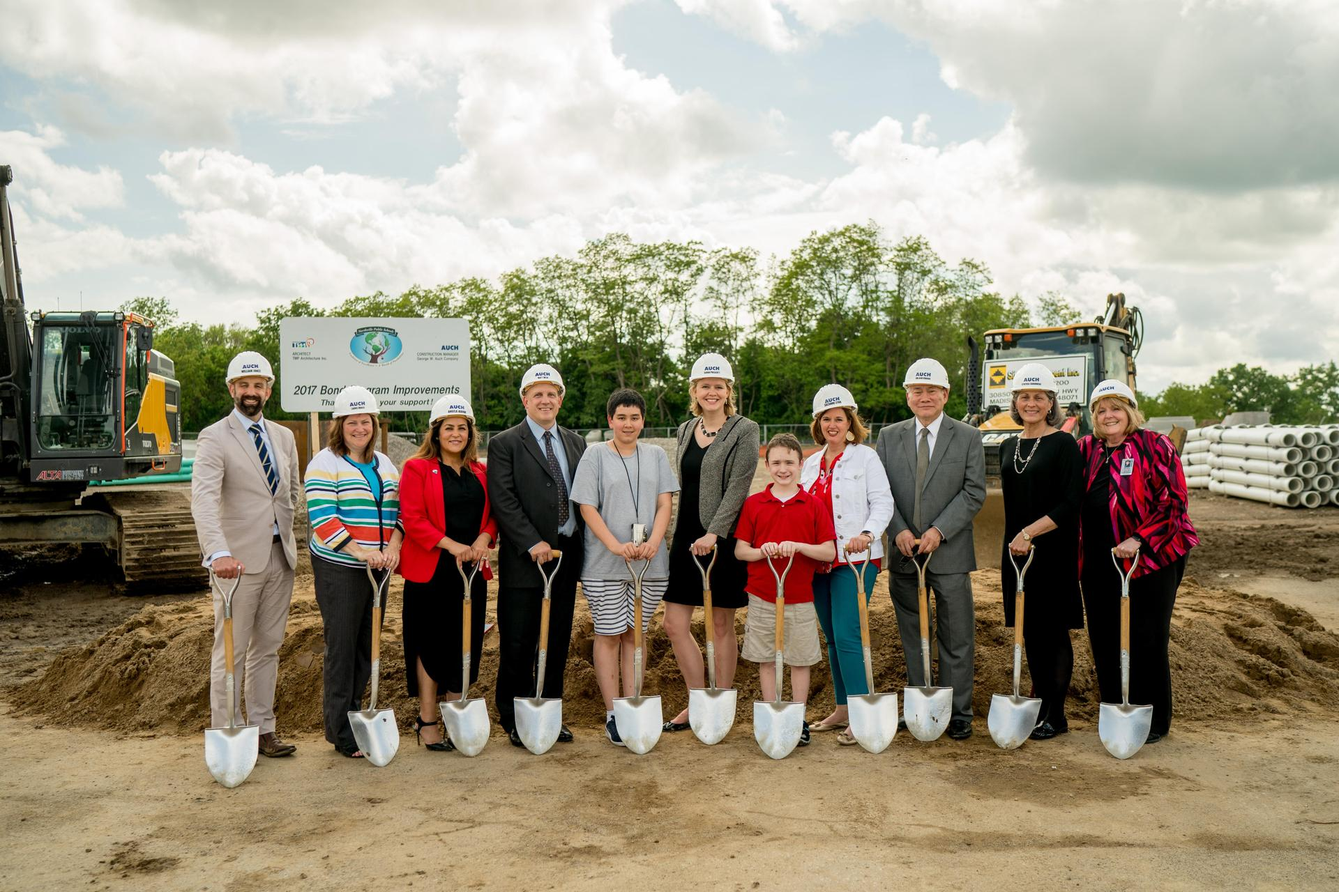 Board of Education and Administrators stand at the Hillside groundbreaking site.