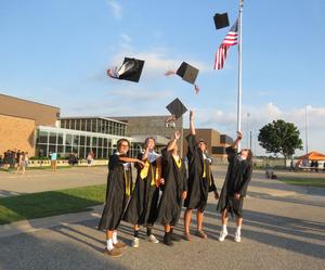 Seniors enjoy the traditional toss of the caps after graduation.
