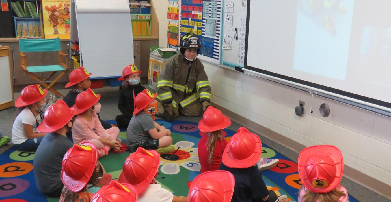 Kindergarten students learn about fire safety via a Zoom meeting with a firefighter.