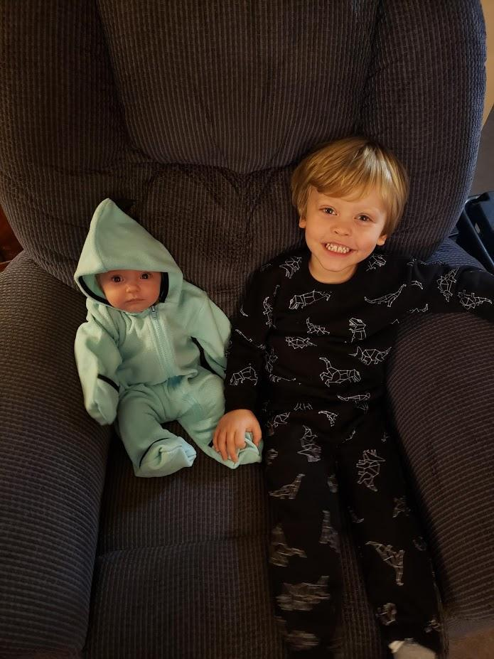 Baby in a sea foam green hooded fleece romper sits on a dark blue armchair next to a blonde three-year-old boy who is smiling and wearing a black sweatshirt and sweatpants with white dinosaur constellations on them