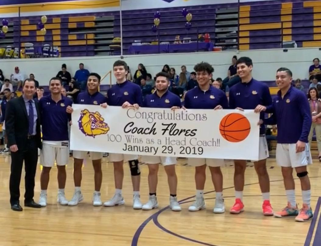 Coach Flores with his team and 100 win banner