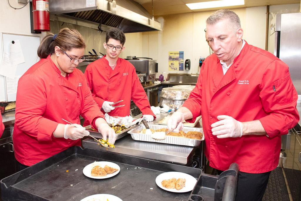 Students and staff prepare chicken cordon bleu inside the Connolly Center kitchen