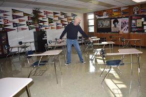 man standing between two desks