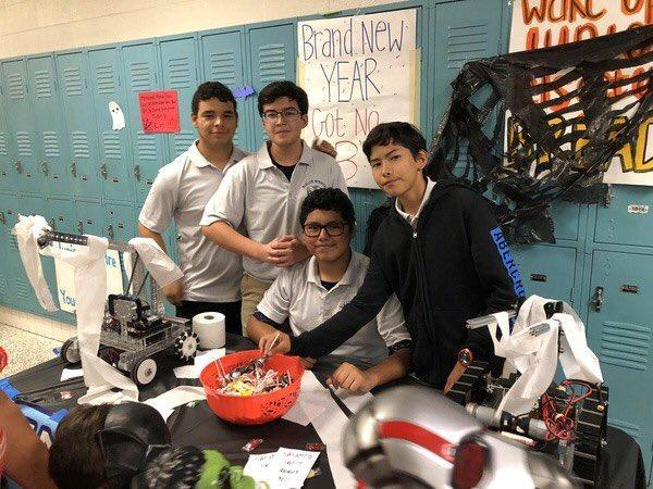 students in front of lockers displaying robot on the table in Halloween