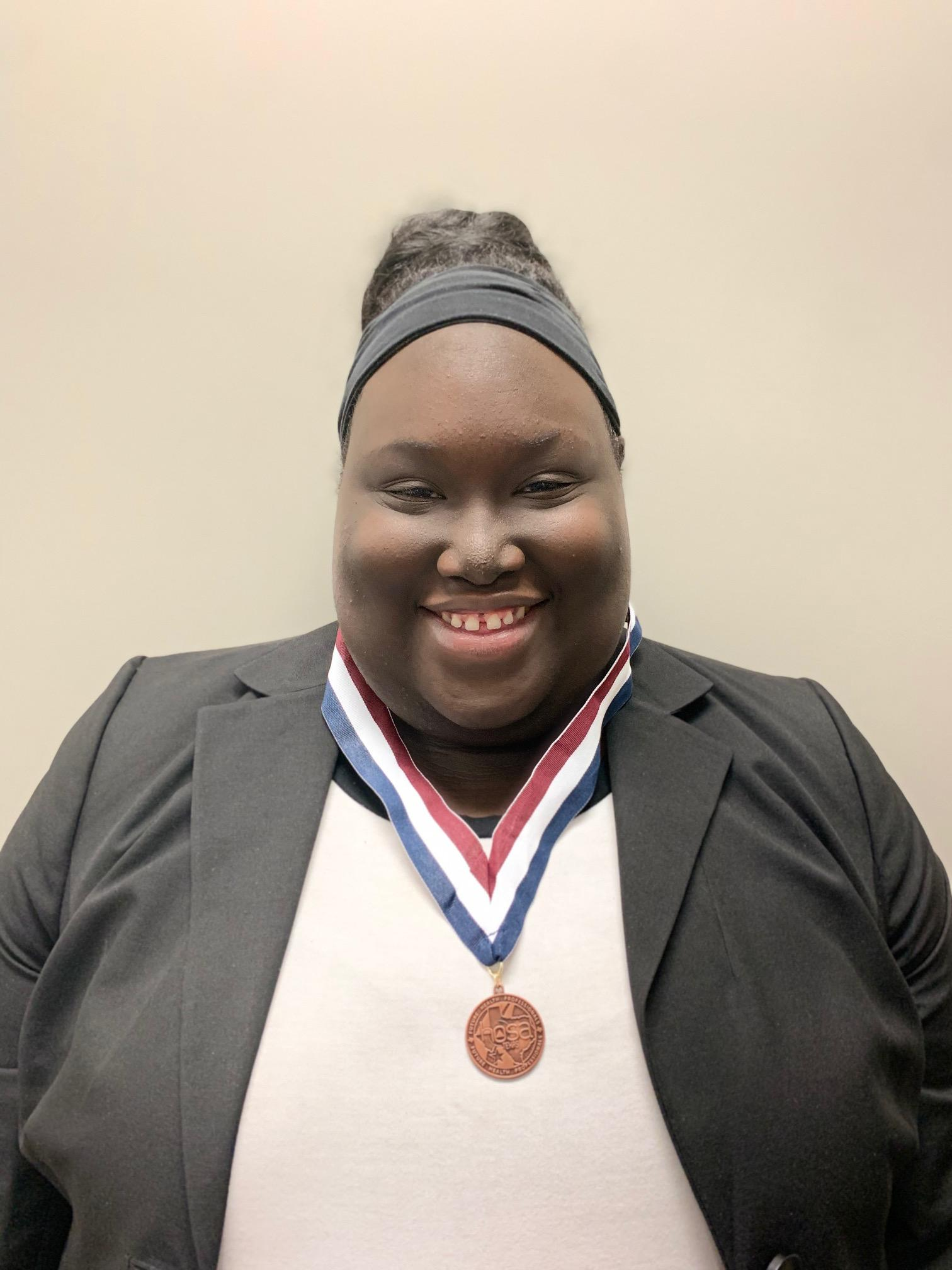student wearing medal she earned