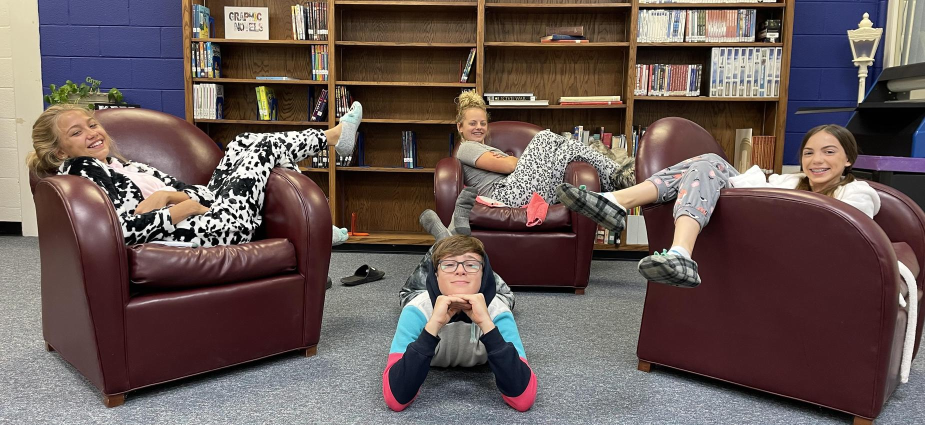 Four students wear pajamas in a library.