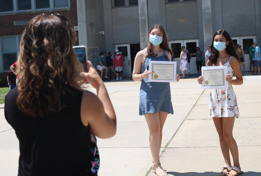Photo of two Edison 8th graders posing with promotion certificates as mom takes a picture.