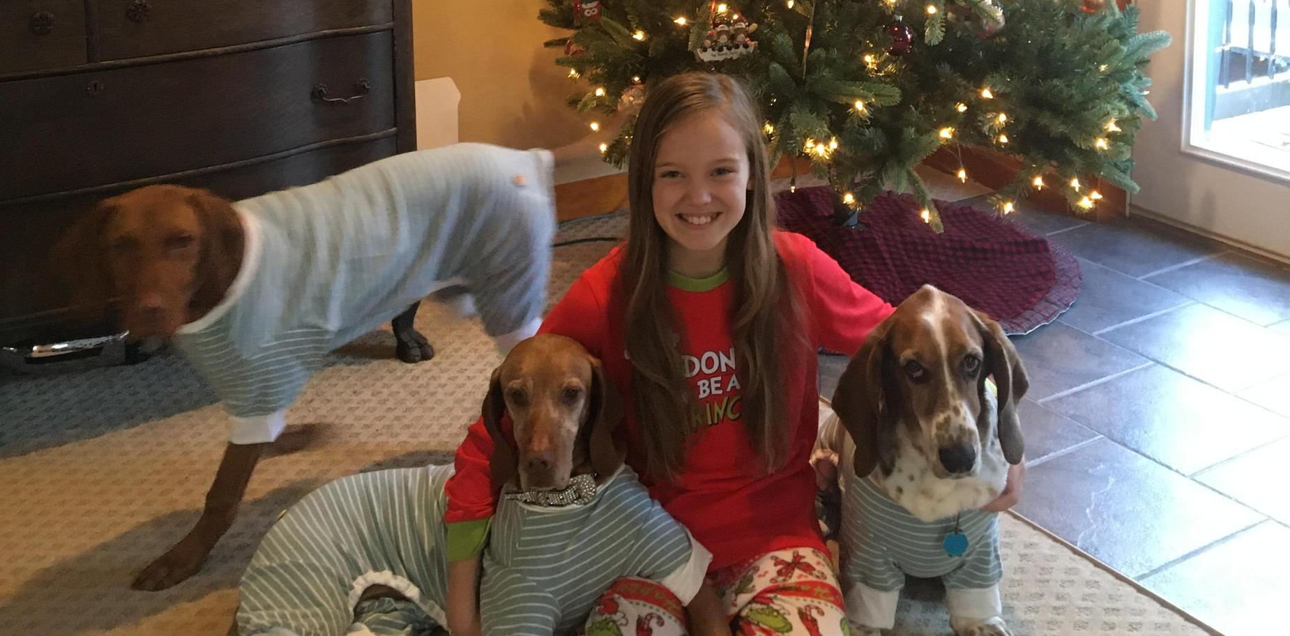 Student in holiday attire with her dogs
