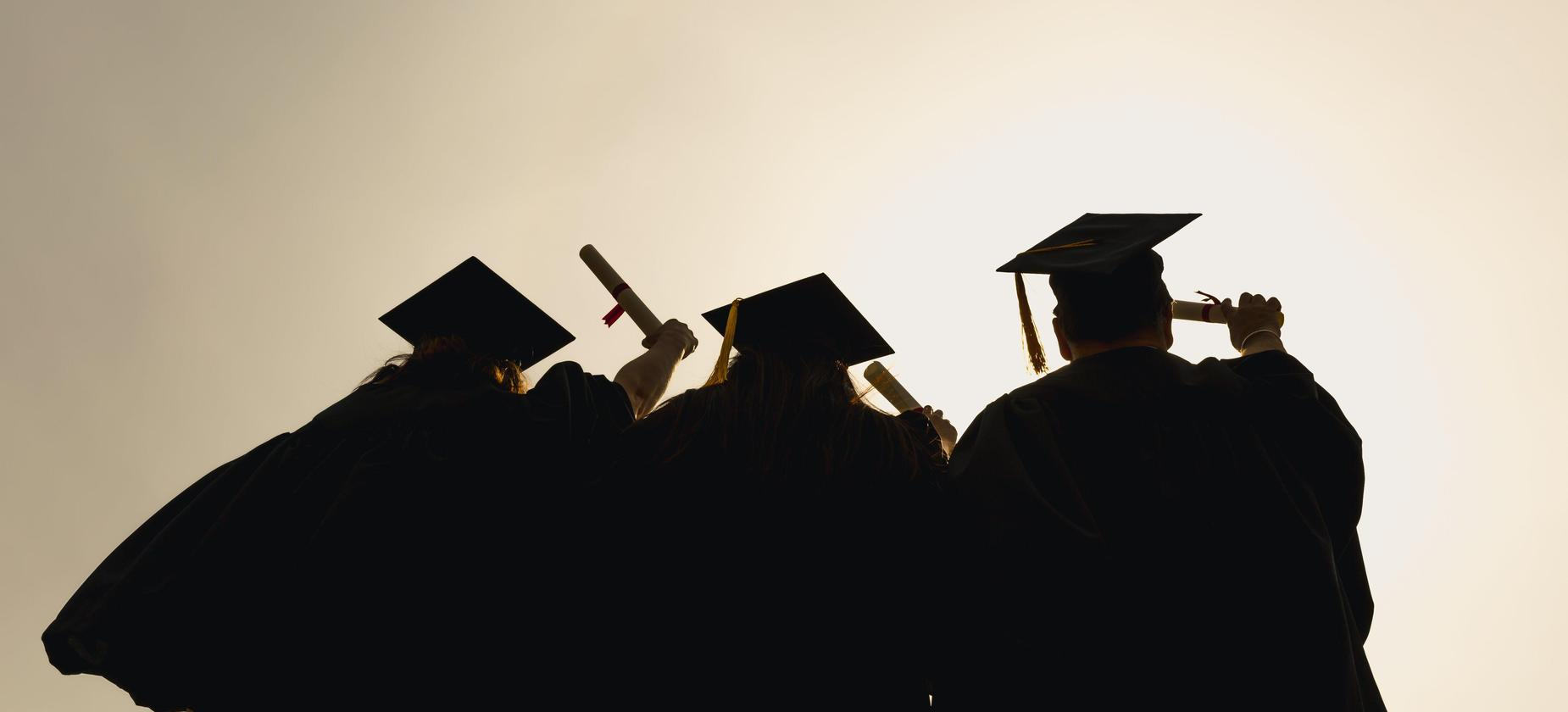 Students in graduation caps and gowns viewed from behind