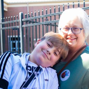 pre teen boy hugging grandmother