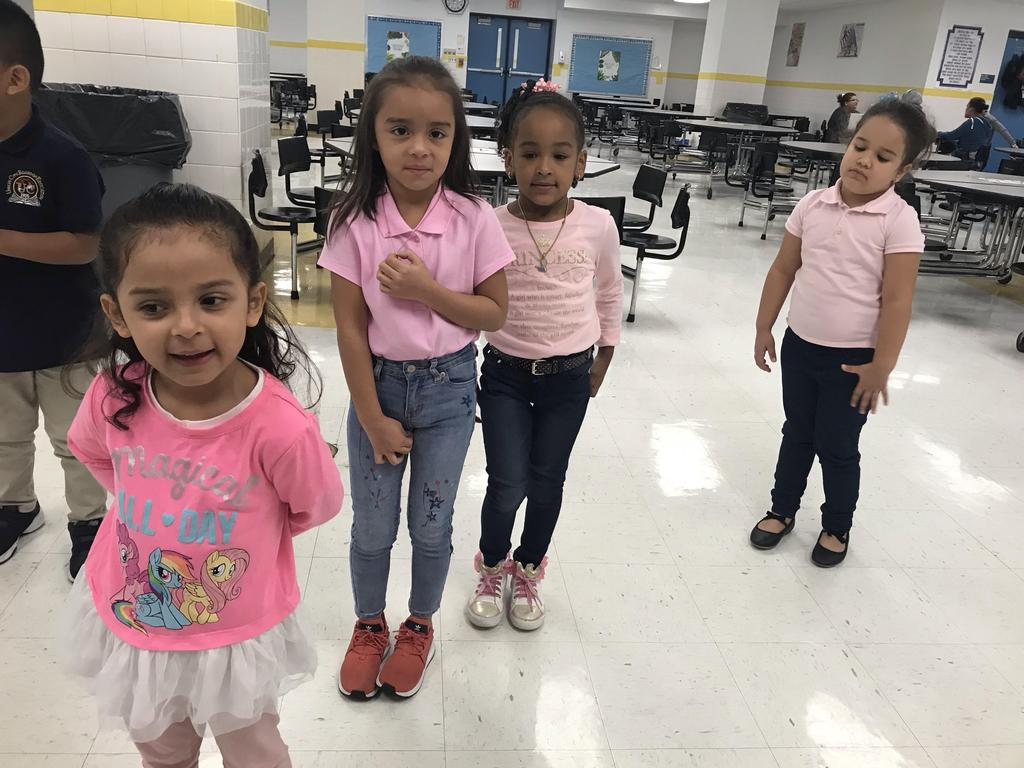 four young girls proudly wearing pink for cancer awareness