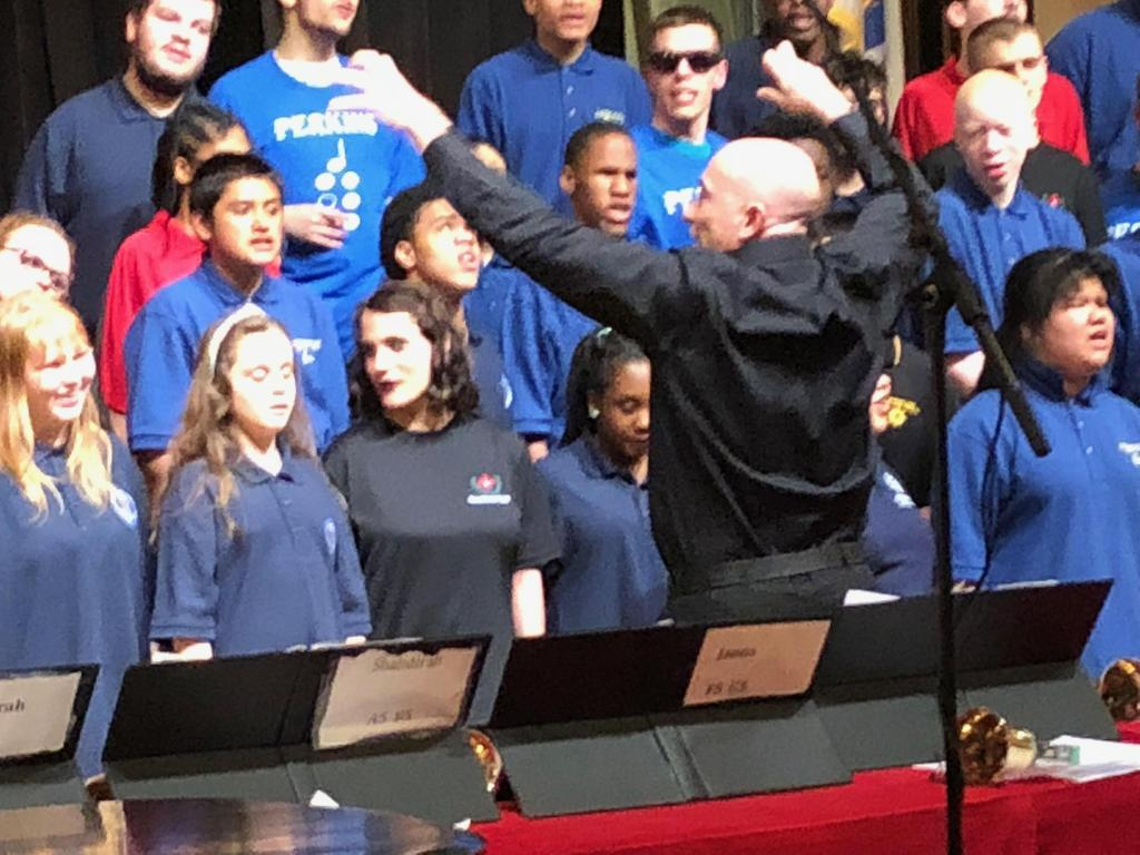 Mr. Naum conducting the united choirs during the performance Saturday evening.