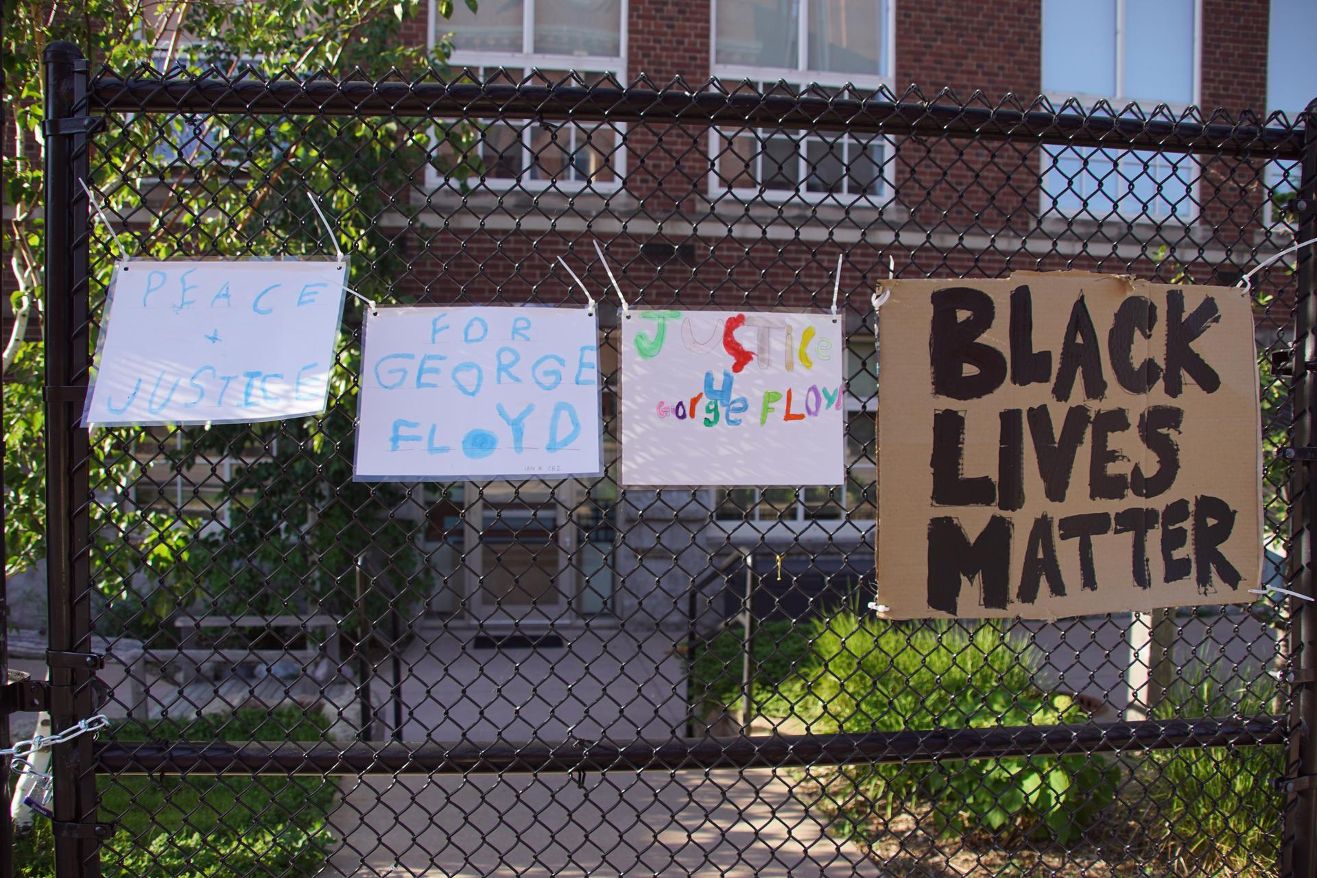 Signs on 38th street fence, including Black Lives Matter