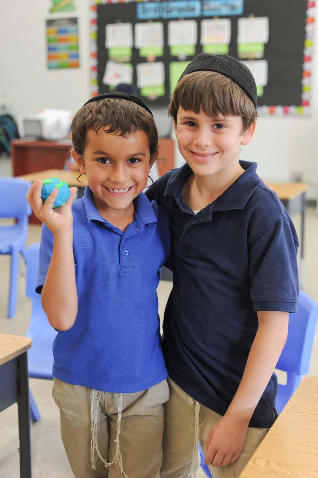 Boys smiling with clay model of Earth