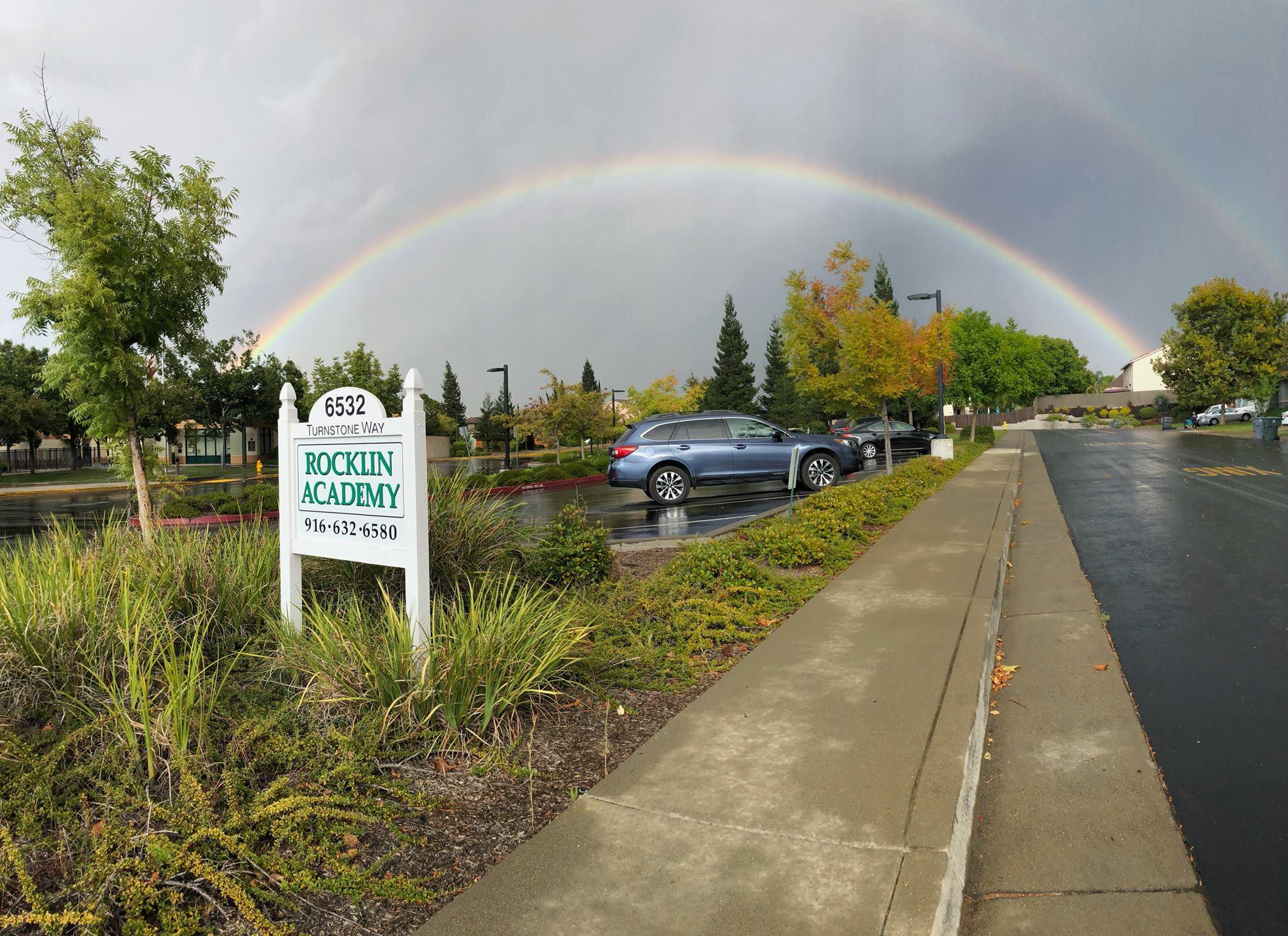 Rocklin Academy Turnstone sign with rainbow on a rainy day