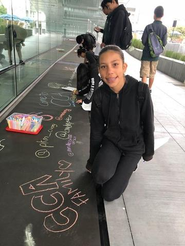 "A CCA student who has written, ""CCA Family"" in chalk."