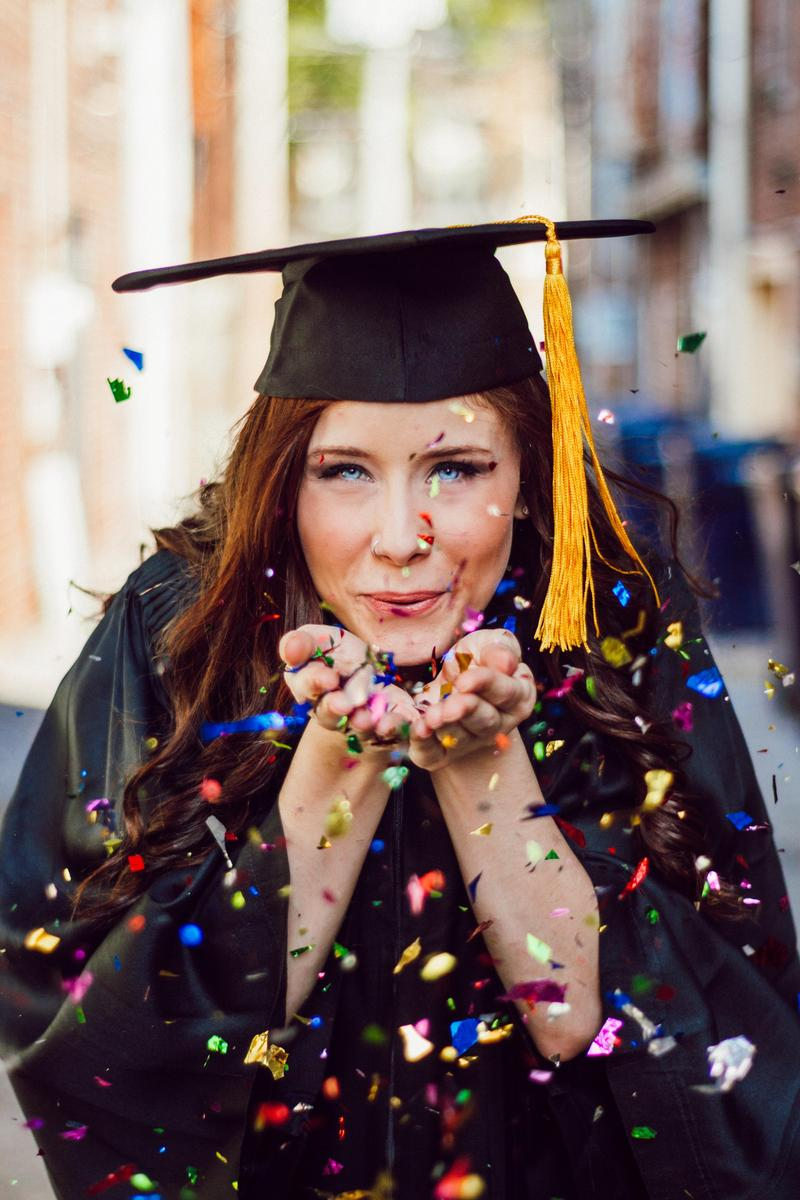 female graduate in cap and gown blowing on confetti