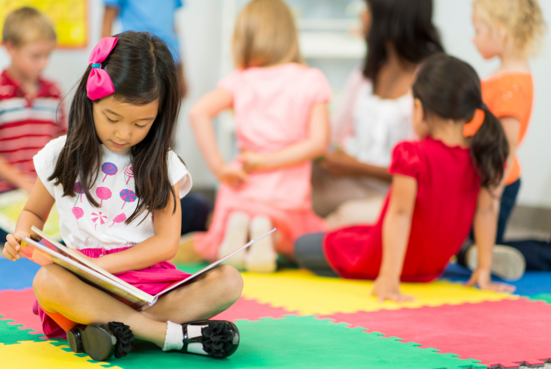girl with pink bow reads a book in front of other preschoolers on the floor at school