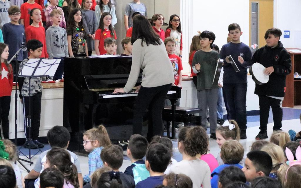 Photo of Wilson 5th graders performing holiday tunes at Lincoln for preschoolers and kindergartners