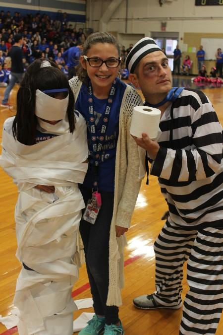 Two sixth graders pose for a photo with Mr. Espino after completing a toilet paper wrapping game at the Fall pep rally.