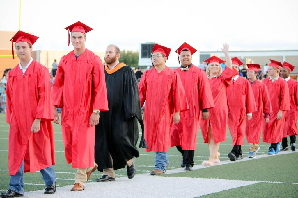 students of the victoria east high school 2018 graduating walking into memorial stadium, smiling and waiving