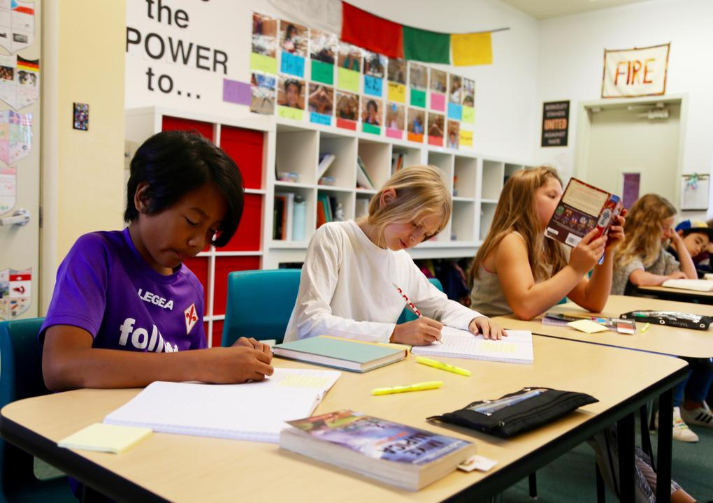 A groups of children sit at a line of desks in a classroom. A boy with dark skin and black hair wearing a purple t-shirt writes in a notebook. A girl with blond hair sits next to him and writes in a notebook. A girl with long, light brown hair reads a book.