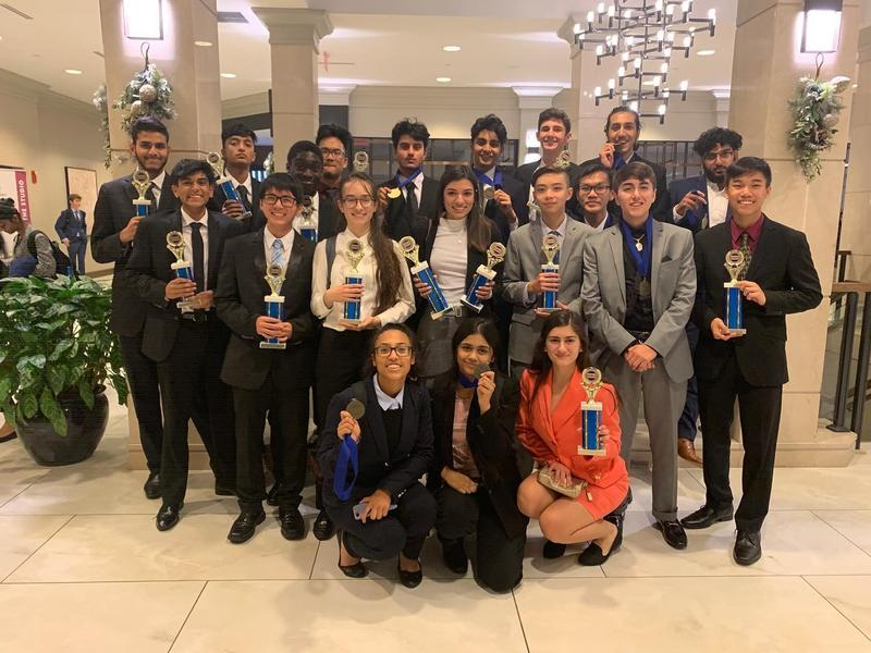 20 Bensalem High School DECA students, 15 boys and 5 girls, dressed in suits and dresses pose with their trophy they earned at District competition. 2 winners were not photographed.