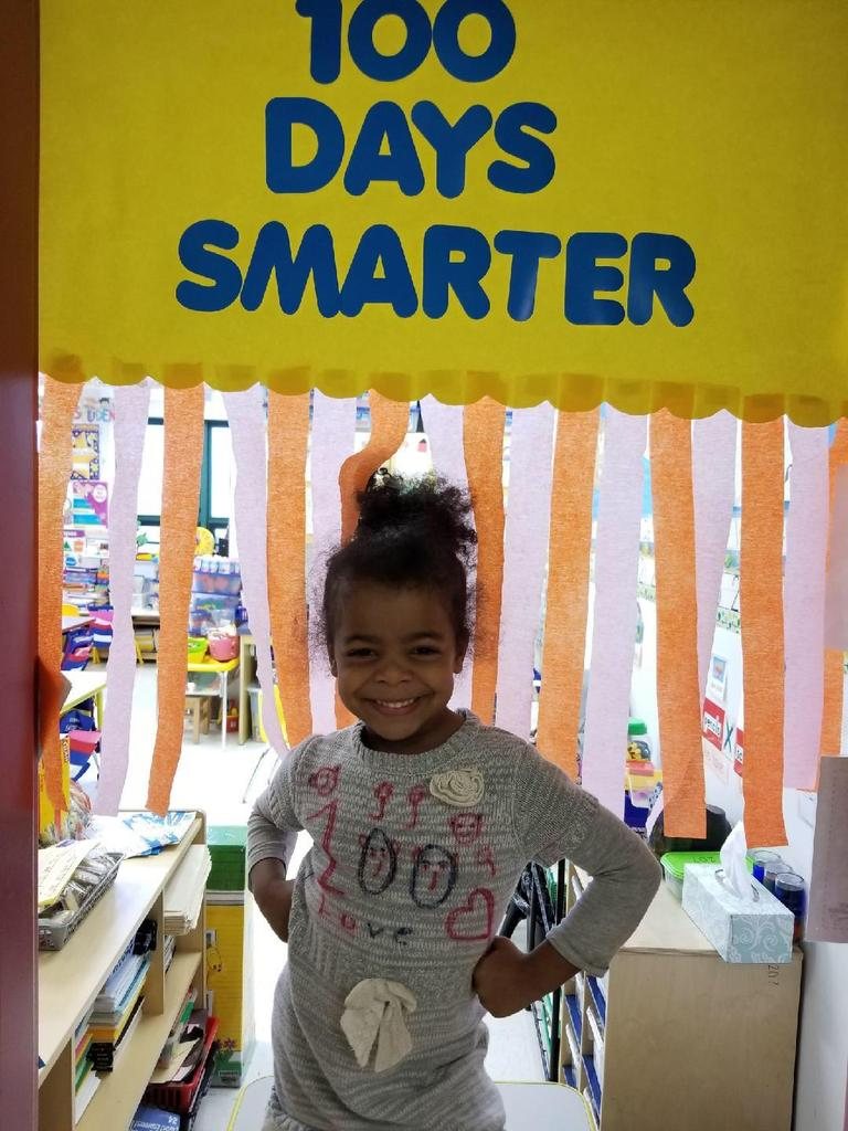 girl posing under sign celebrating 100 days of school