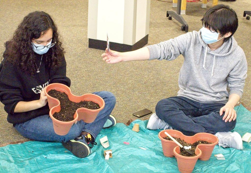 Two students sitting on the floor, working on a gardening project