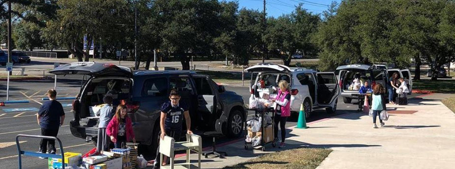 Students loading items into cars for delivery to Provisions Outreach