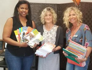 Dr. Cherise Moore (left) presents books to West Ranch Wellness Center Coordinator Nancy Phillips with WiSH Education Foundation's Amy Daniels
