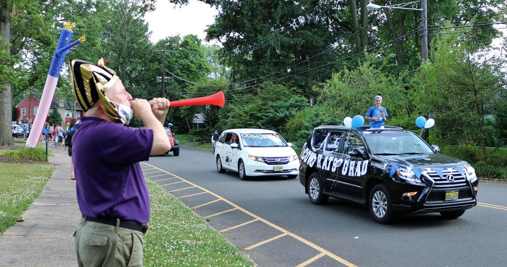 Photo of Washington principal blowing horn as 5th graders and families pass by during Grade 5 Clap Out Car Parade.