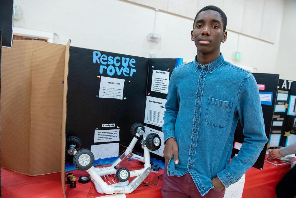 A student next to his project called Rescue Rover