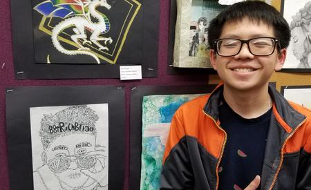 student smiling with artwork