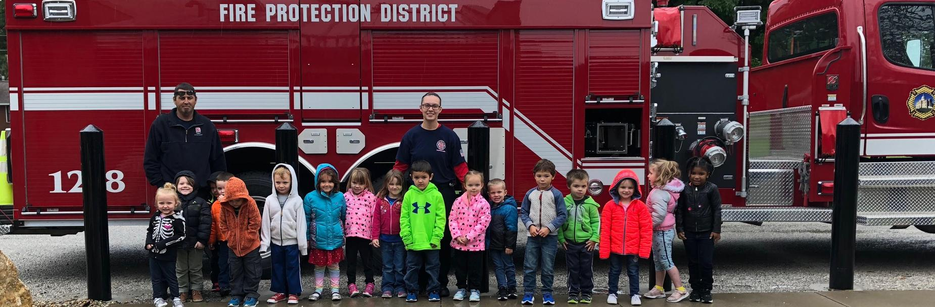 PreK class poses with firetruck