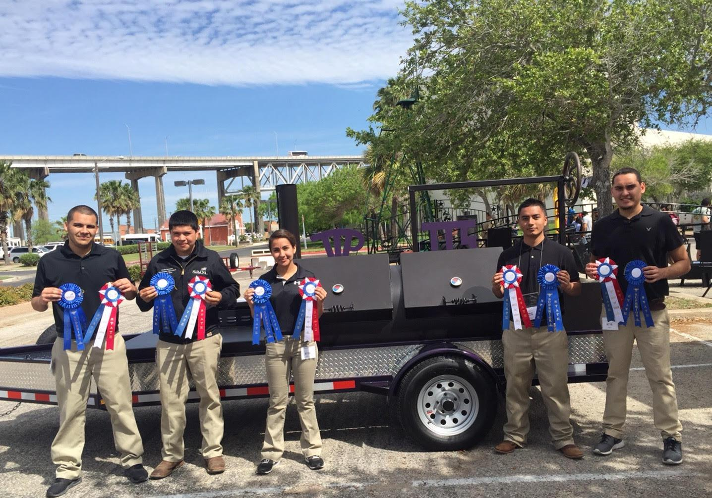 group of welding student in front of project they made holding blue ribbons