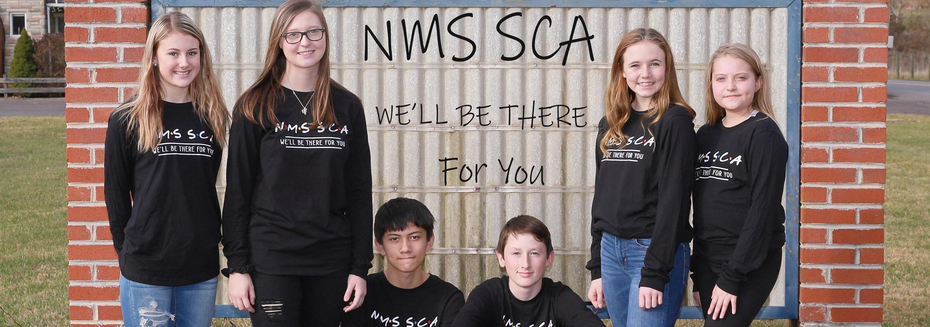 NMS SCA member infront of the NMS sign