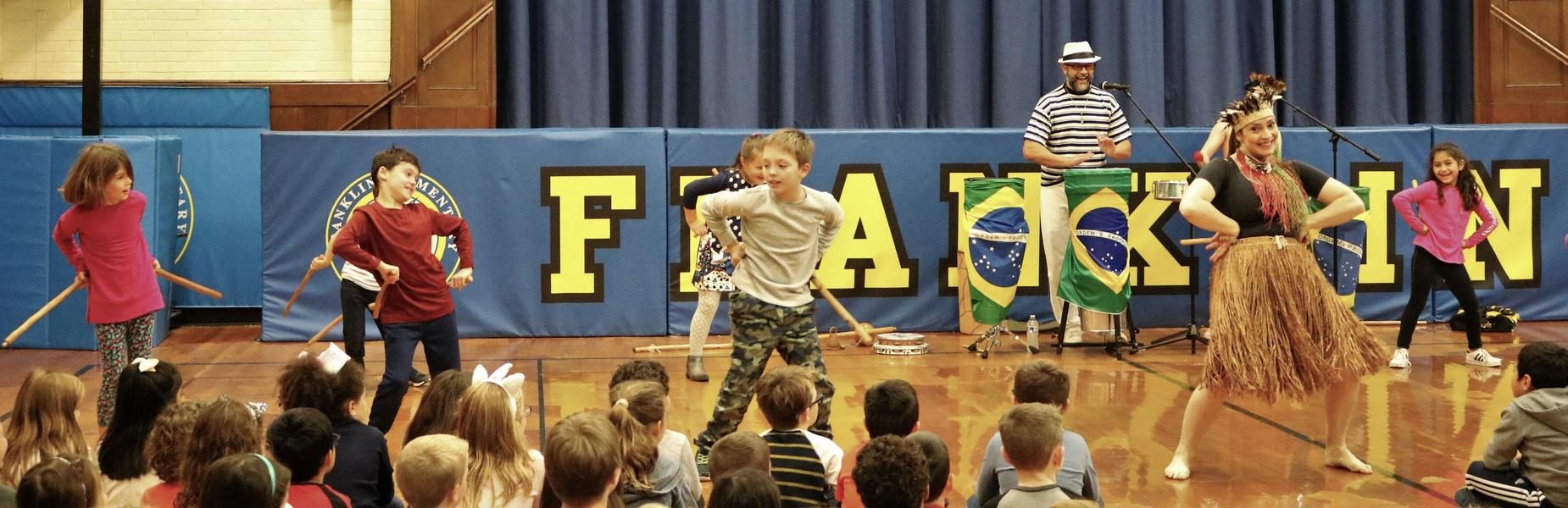 Franklin School students enjoy a lively performance by Ginga Brasileira on Nov. 19 as students explore the history, language and culture of Brazil through music and dance.  The dancers enlisted students in performing the Maculele, a stick dance from the Brazilian sugar cane plantations, while showcasing other dances including the Capoeira which combines dance, martial arts, and music. The event is part of a cultural arts program provided by the school's Parent -Teacher Organization.