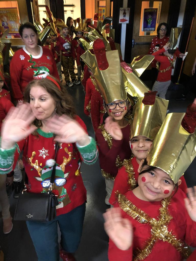 teachers with ugly sweaters and children dressed toy soldiers ready to perform