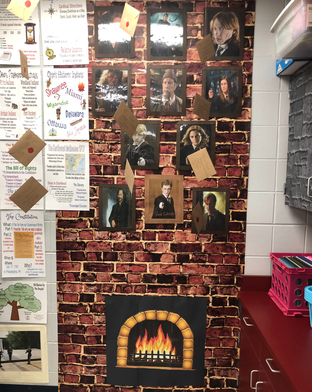At the back corner of the room is a fireplace with letters making their way out. Above it are some of my favorite characters and their families.