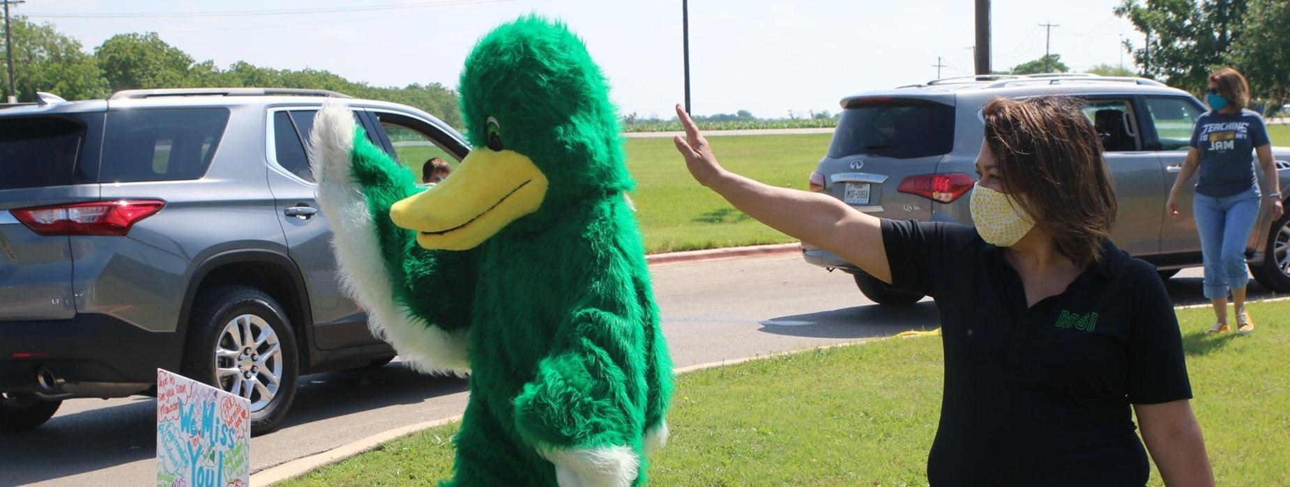 Principal and mascot waving at cars.