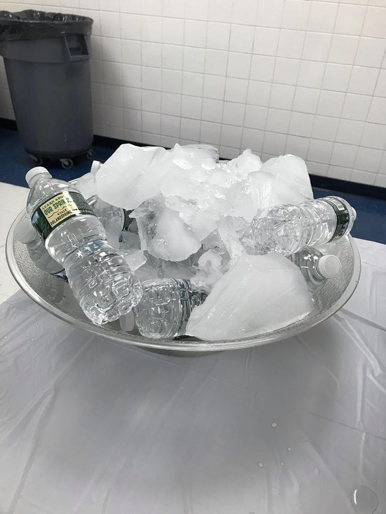 a bowl of chunks of ice with bottled water at the head table