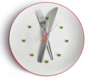 A photo that represents dinner time. It is a clock made of a white plate , fork and a knive acting as Minute and Hour hand and Peas at clock times.