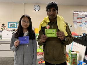 Two students standing and holding inspirational messages meant to destress the test.