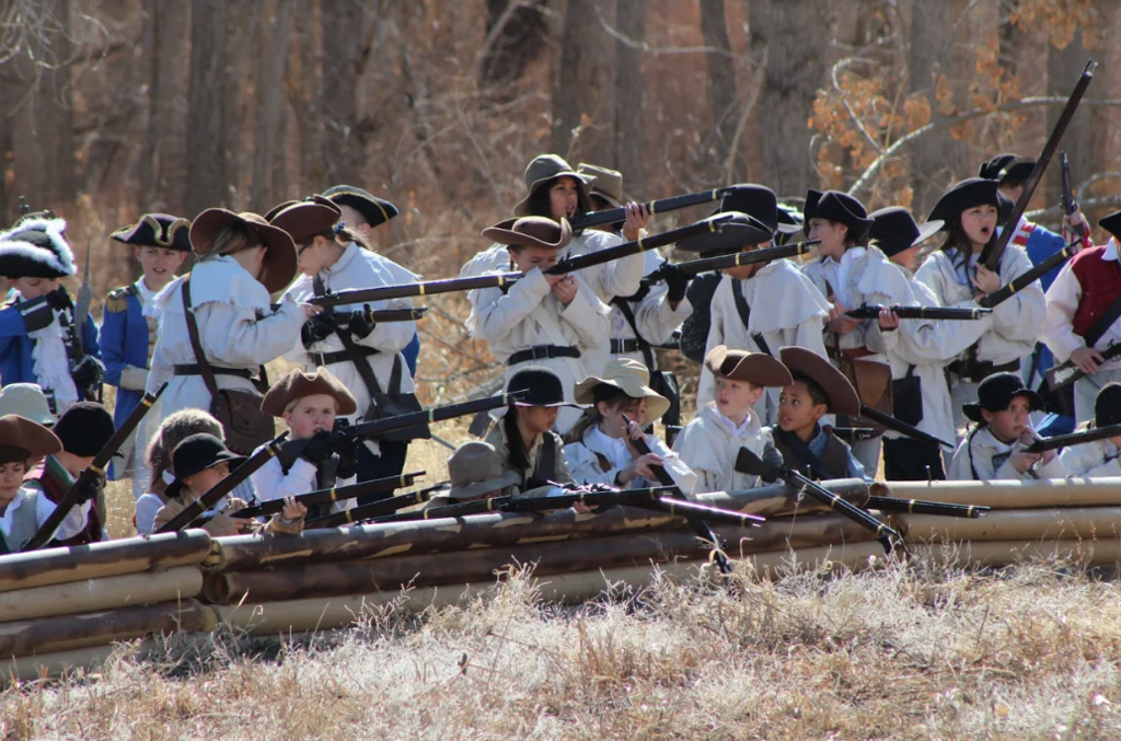 Fifth graders participate in a Revolutionary War Battle Reenactment after four weeks of training.