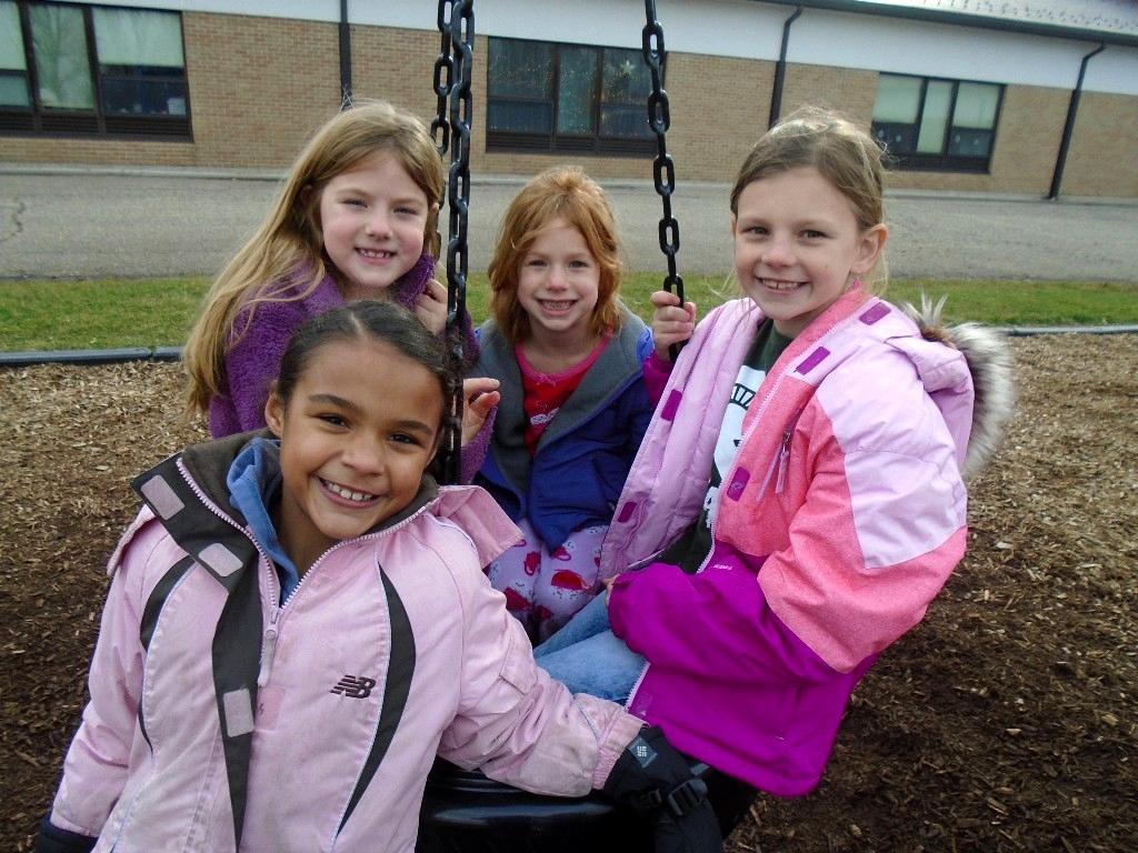 four girls pose on swingset