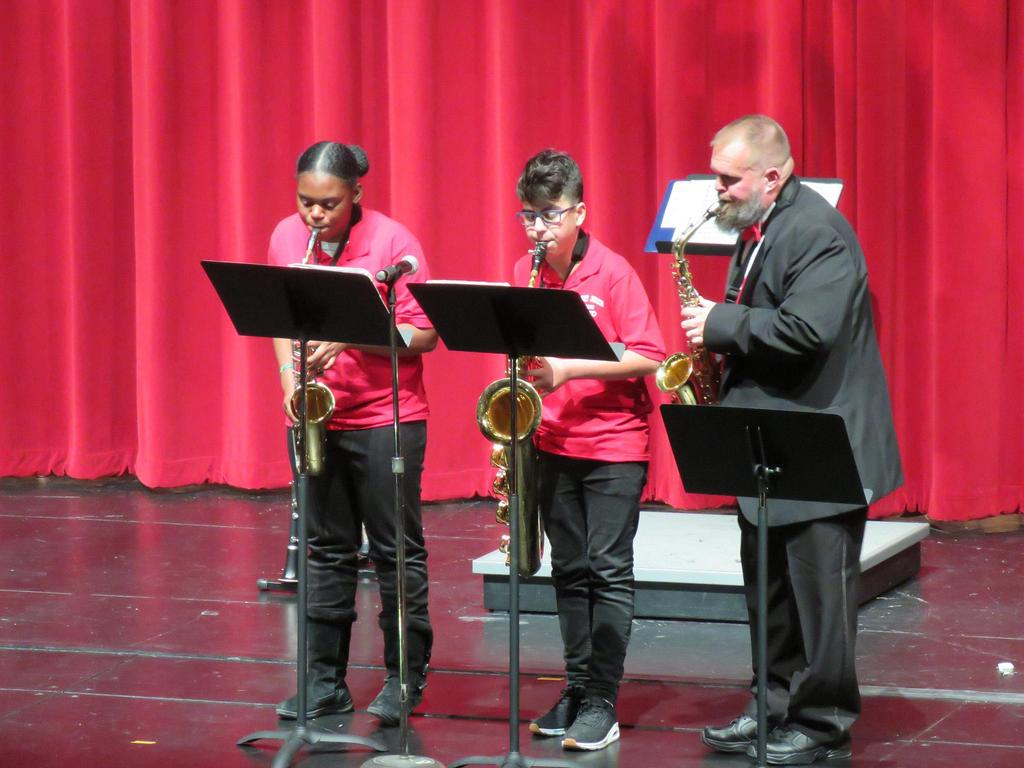 Two horn players and a teacher perform on stage