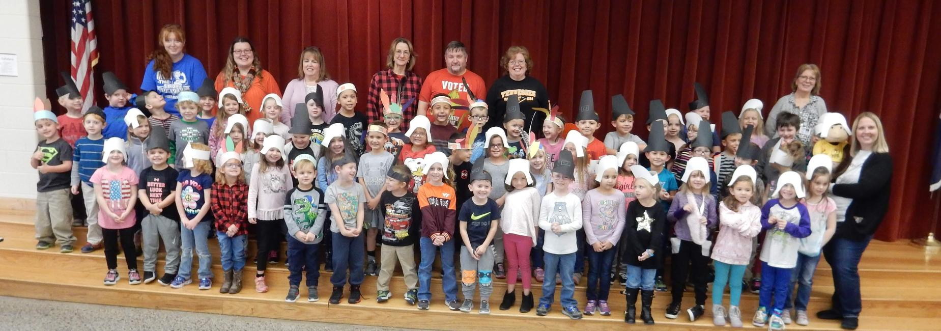 Kindergarten students dressed as pilgrims and native Americans for an early Thanksgiving feast