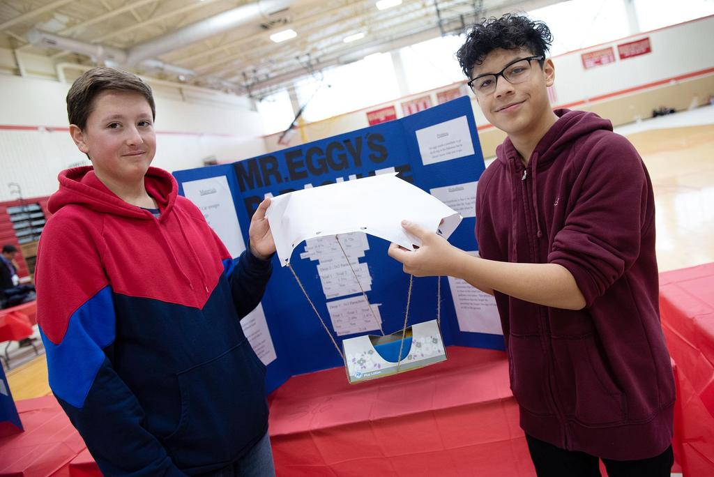 Two students hold a parachute-like egg-drop device
